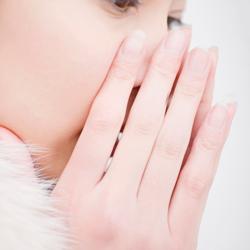 口に両手を当て息を吹きかける女性