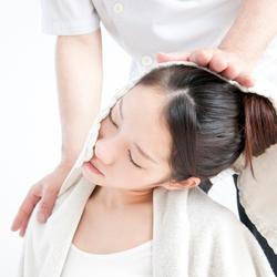首の筋肉を伸ばすストレッチを受ける女性