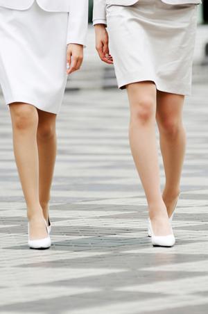 膝上のスカートを履いた女性二人の足のアップ